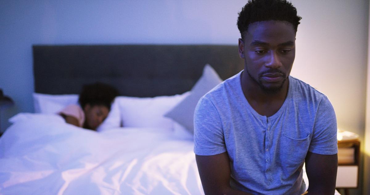 Wide awake man can't fall asleep in bed