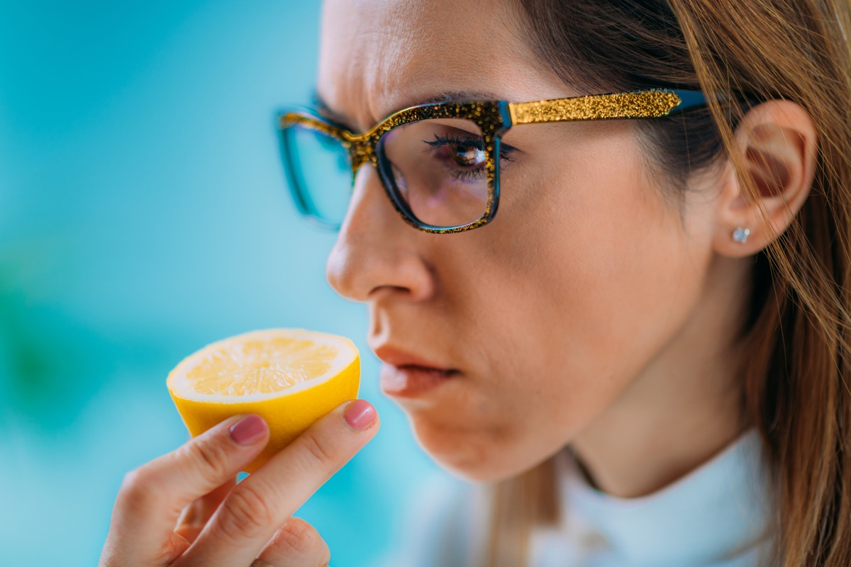 Woman trying to smell lemon lost sense of smell