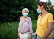 Mother and daughter with protective face mask, walking down street and talking