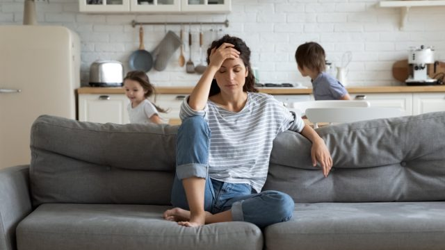 Woman with children experiencing anxiety and stress at home