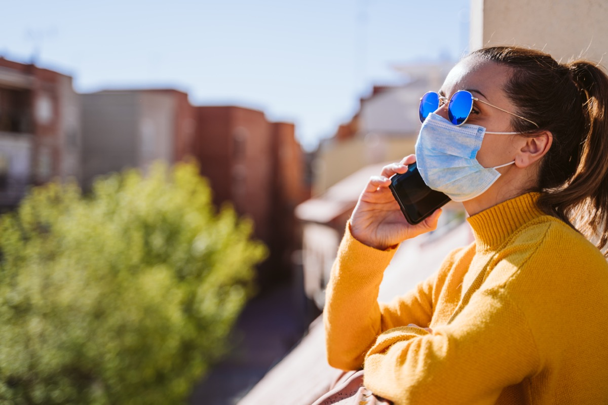 young woman at home on a terrace wearing protective mask, using mobile phone and enjoying a sunny day. Corona virus Covid-19 concept