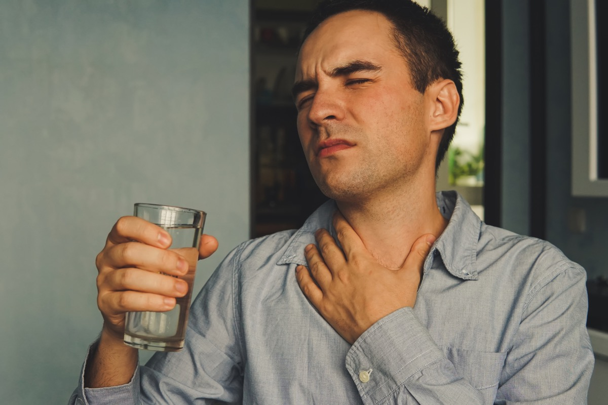 Man drinking water to cure dry throat