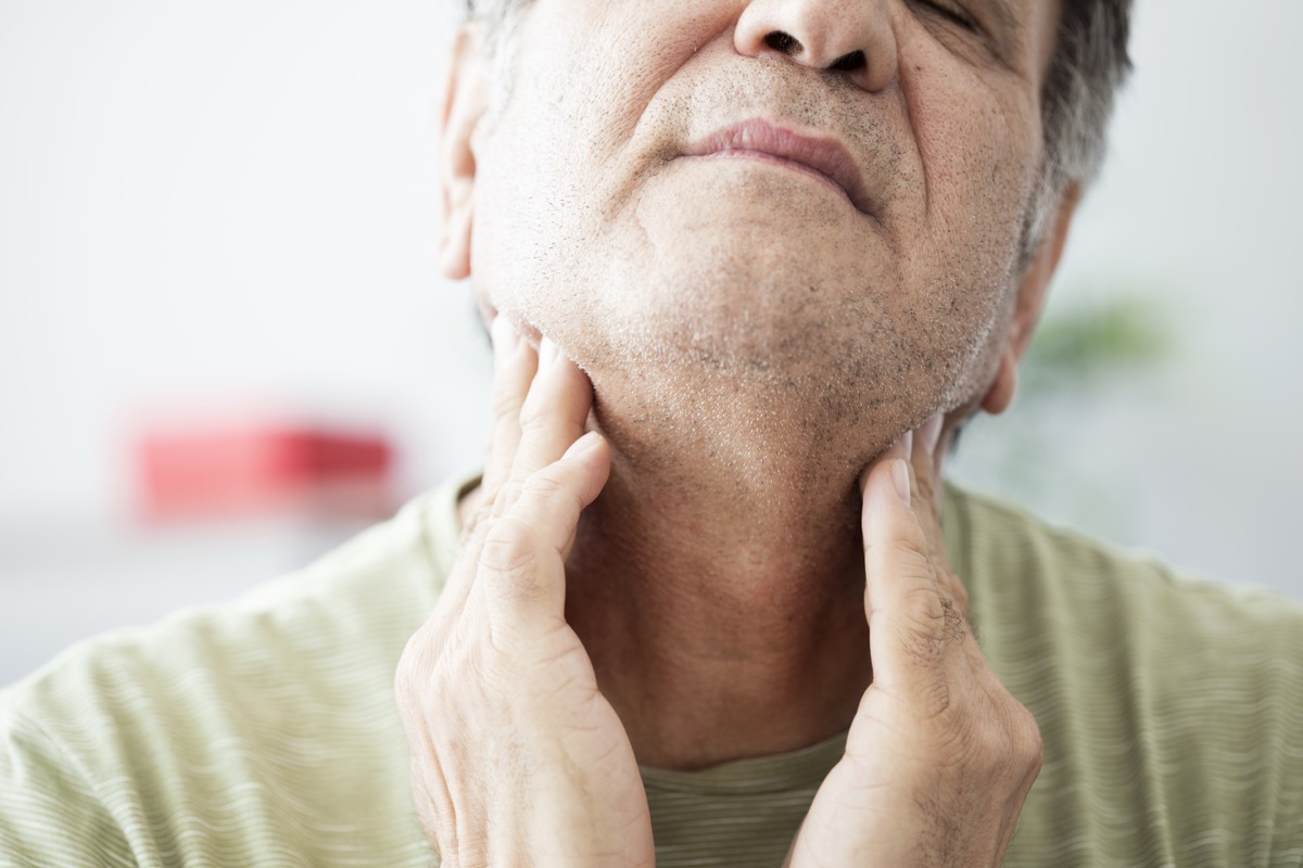 Old man feeling pain in the throat or thyroid