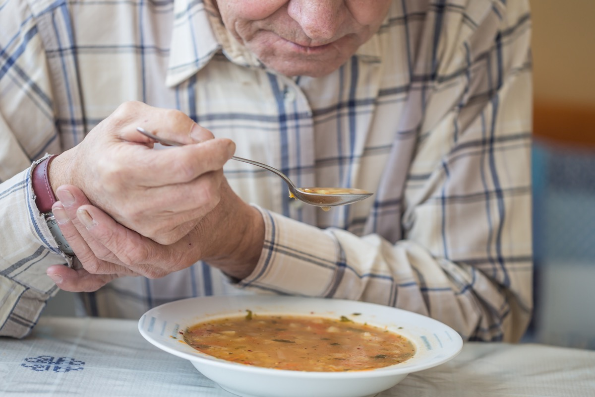 Man with tremors holding hand still to eat soup