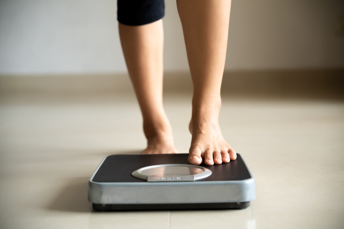 Woman stepping on scale to check weight