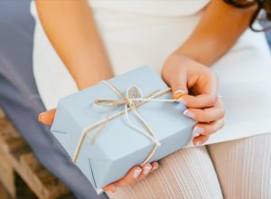 white hands opening ribbon on gift wrapped present