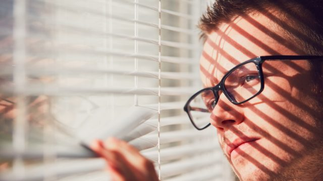 Man looking out window during quarantine