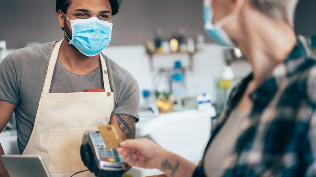A woman wearing a face mask pays for a coffee with a credit card from a young male barista who is also wearing a face mask and smiling.