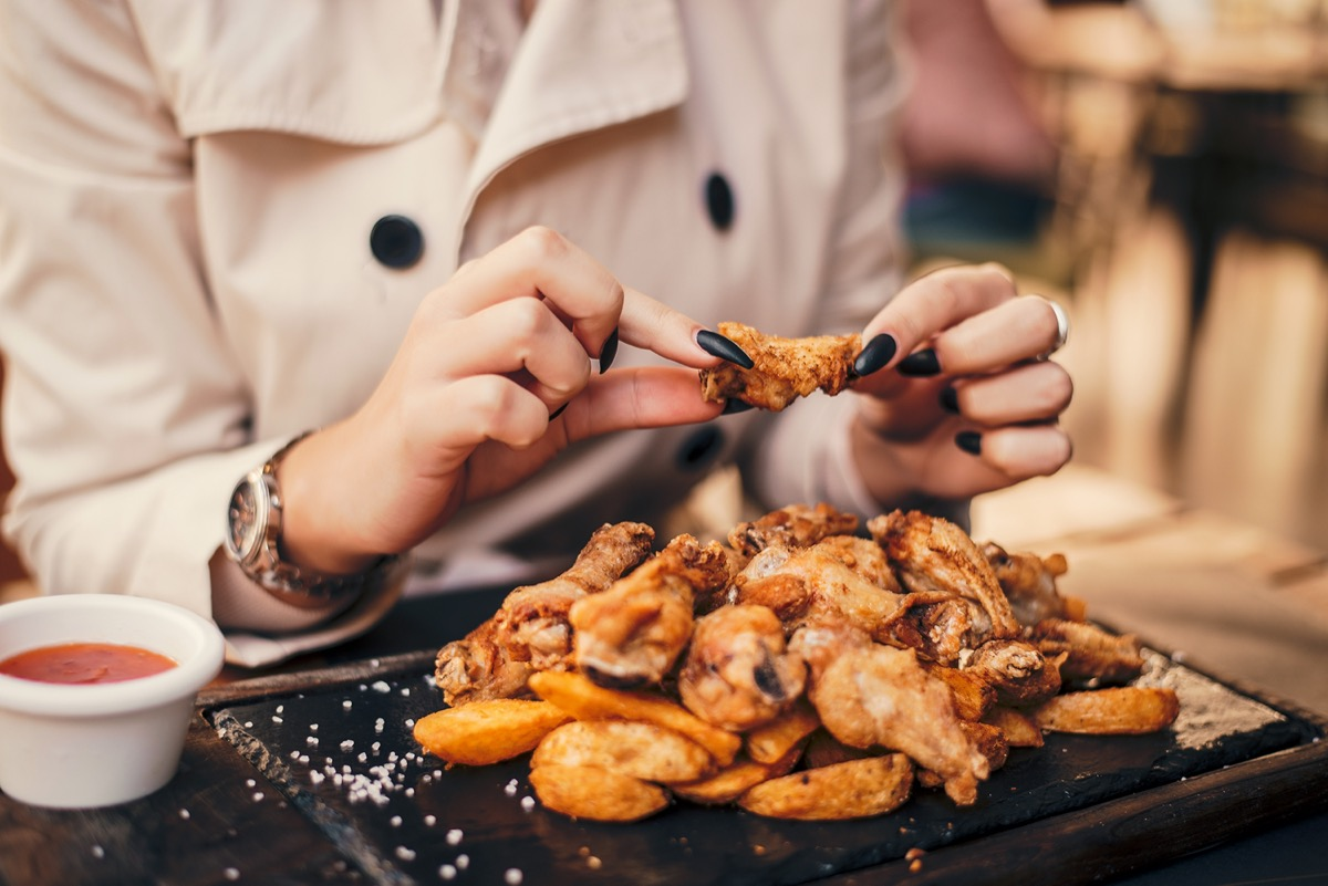 woman with black nails eating chicken wings