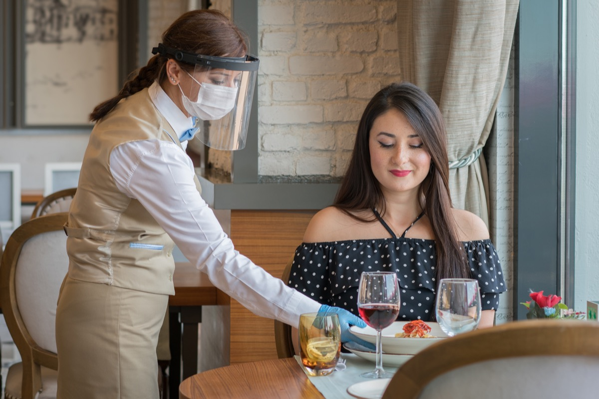 Waiter serving food in a luxury restaurant with face mask Covid 19