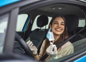 Young woman of color taking off mask in car amid coronavirus