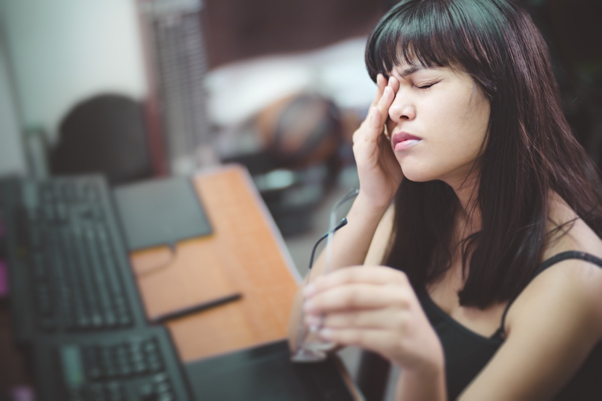 young woman rubbing her eye and holding eyeglasses. She is suffering with aching eyes while working long hours on computer at home.