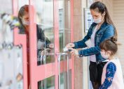 A woman wearing a face mask opens the door to a store with a napkin to prevent the spread of coronavirus while her young daughter watches