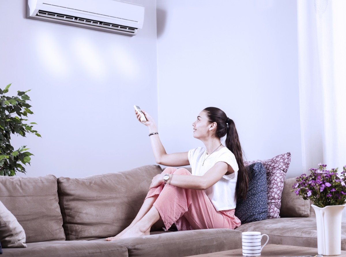 woman using remote control of airconditioner
