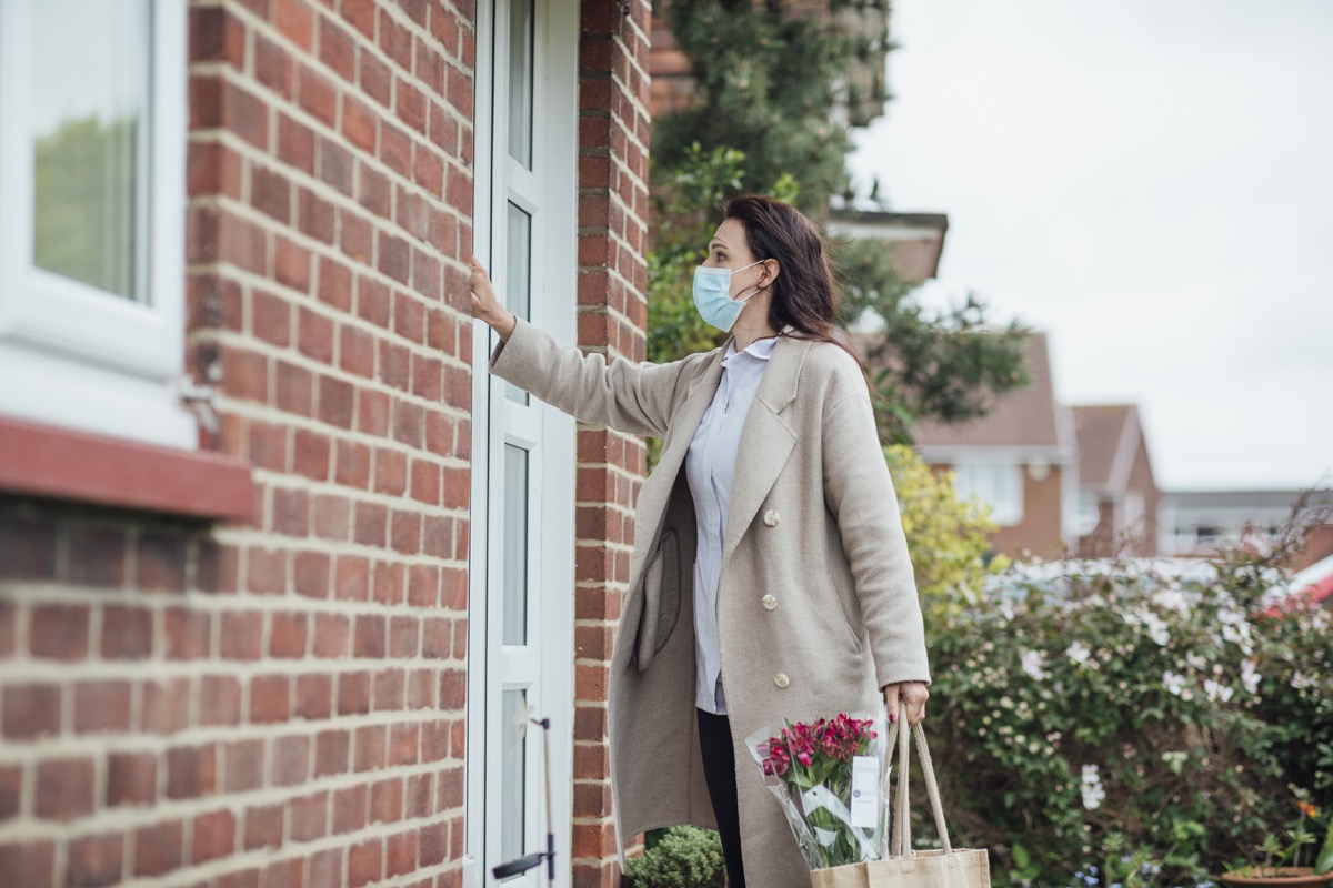 A side view of a female healthcare worker wearing a protective mask knocking on her grandmother's front door, she is dropping off groceries and flowers during the Coronavirus pandemic.