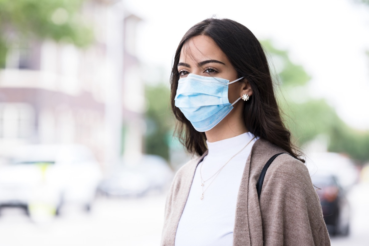 Walking home after class, the young woman wears her protective mask because of the coronavirus epidemic.