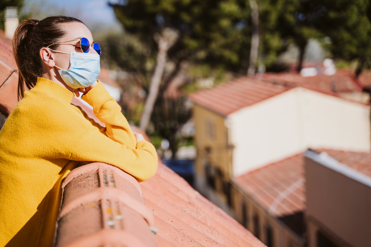 A young woman standing in the sunlight on a balcony because the sun kills coronavirus