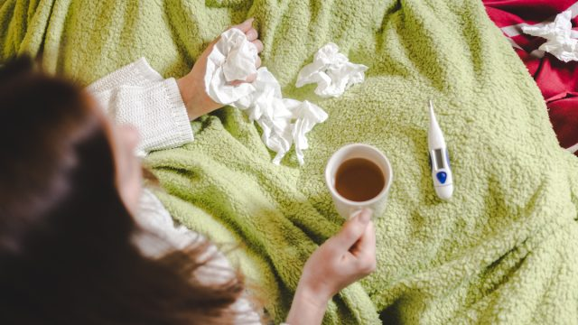 woman shot from overhead while holding tissues and tea, wrapped in a green blanket with a thermometer in her lap