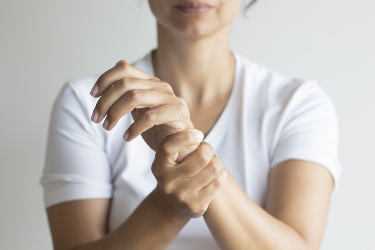 Woman holding wrist from pain