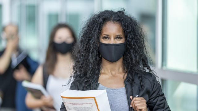 3 students of various ethnicities wearing protective face masks on their college campus.