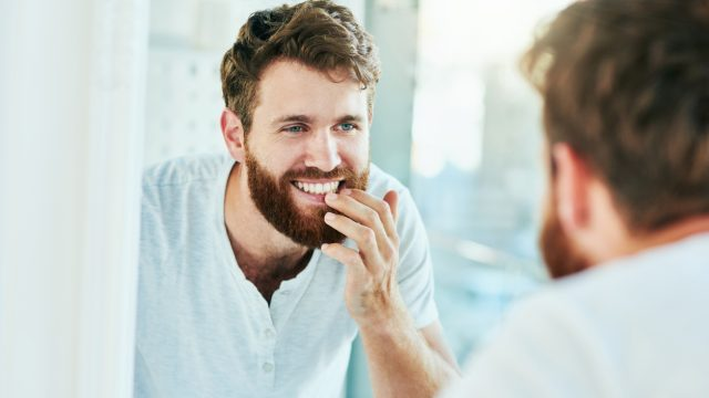 A young man smiling while looking at this teeth in the mirror