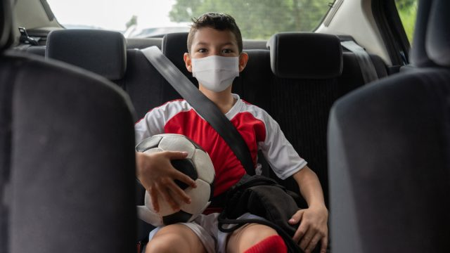 Boy in a car on his way to soccer practice wearing a face mask to avoid the coronavirus pandemic