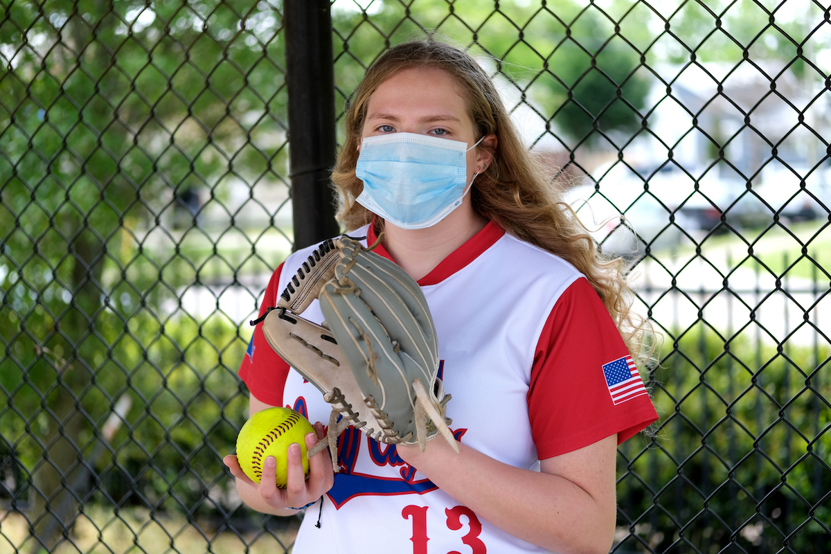 Teenage girl in her softball uniform posing with a healthcare mask to protect her from the Coronavirus