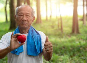 Asian man holding a heart outside