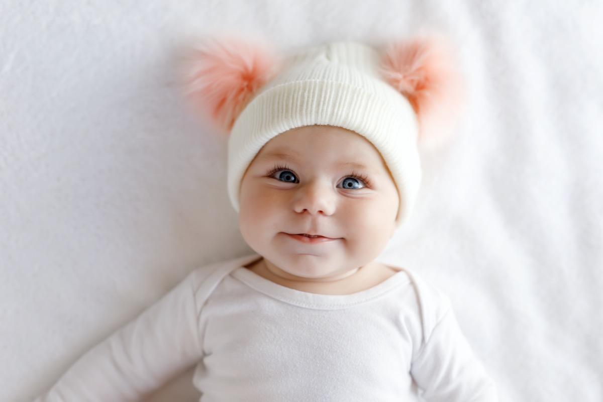 Baby girl in pom pom hat