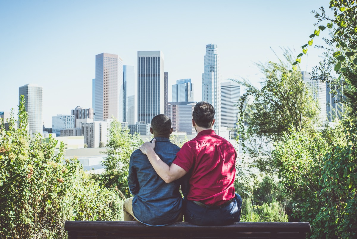 Young gay couple looking at city skyline.