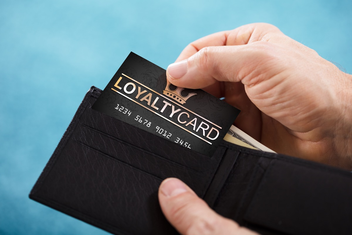 white hand pulling loyalty card out of wallet