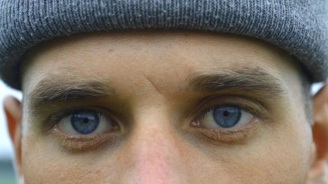 Closeup man with blue eyes and small scar