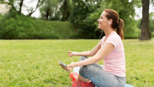 White woman meditating in the park