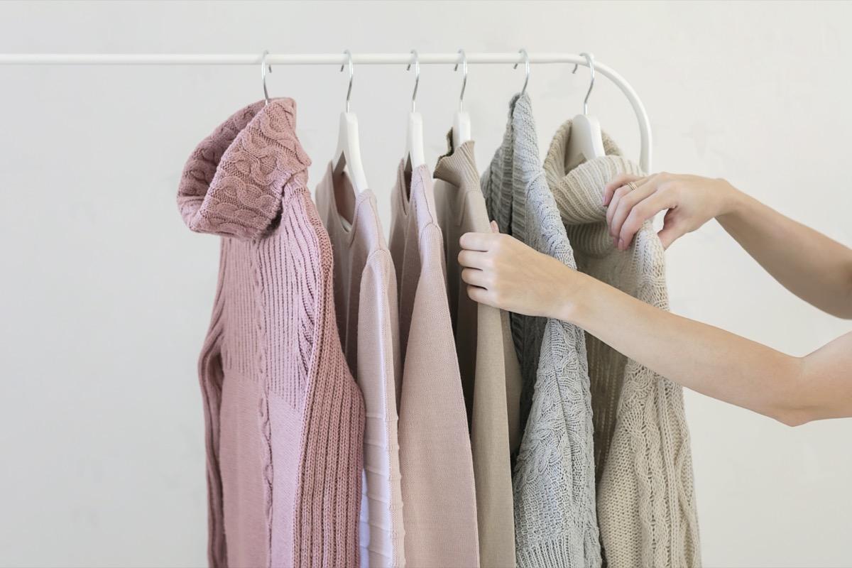 Woman choosing from rack of sweaters