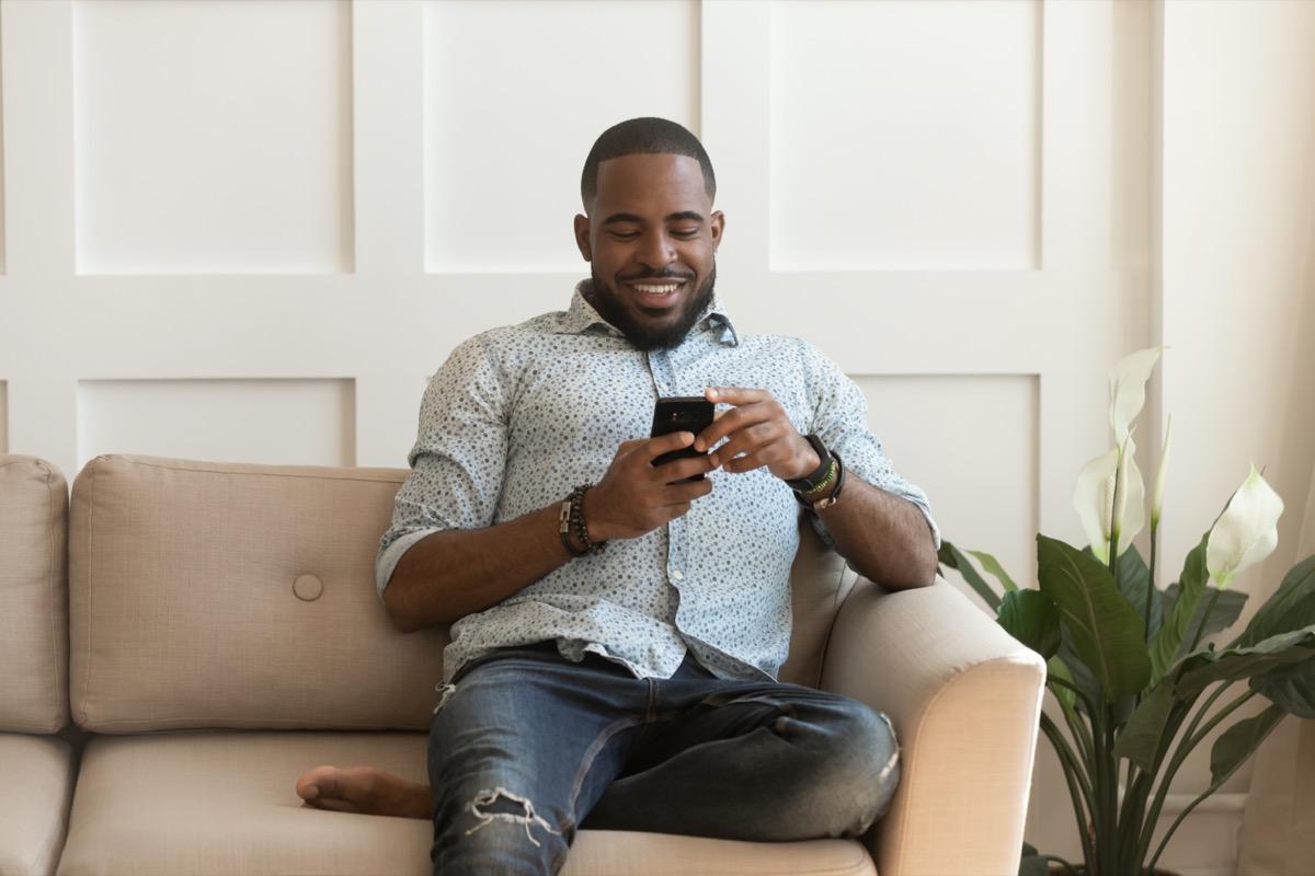 Young Black man smiling at phone