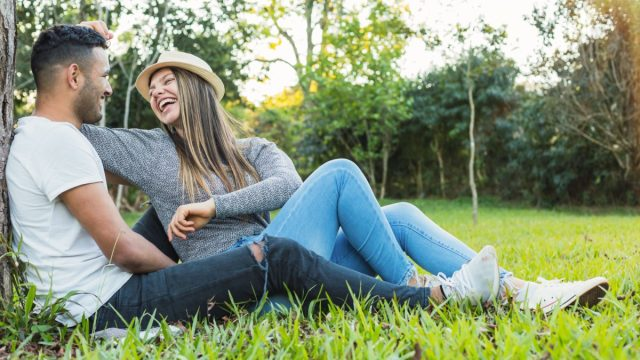 Young man and woman laughing together in park