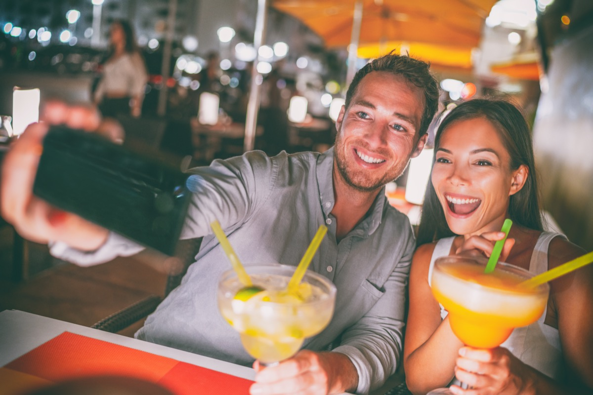 Young man and woman drinking margaritas and taking a selfie