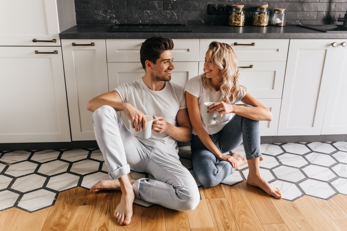 Young white man and woman drinking coffee on kitchen floor