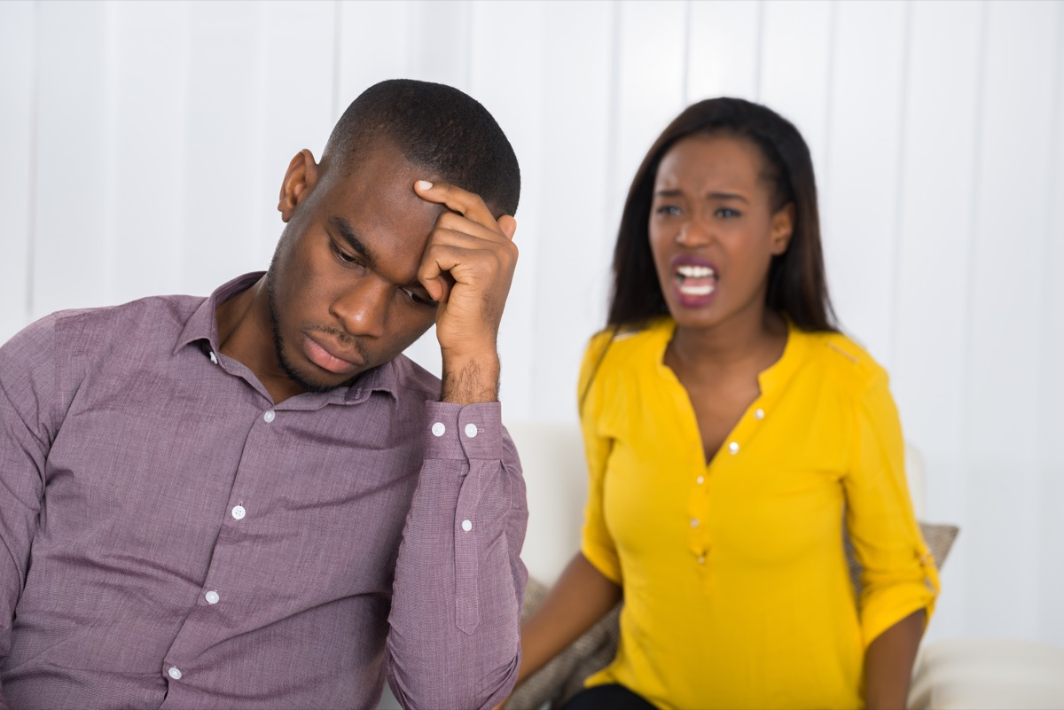 Couple fighting man ignoring woman yelling at him