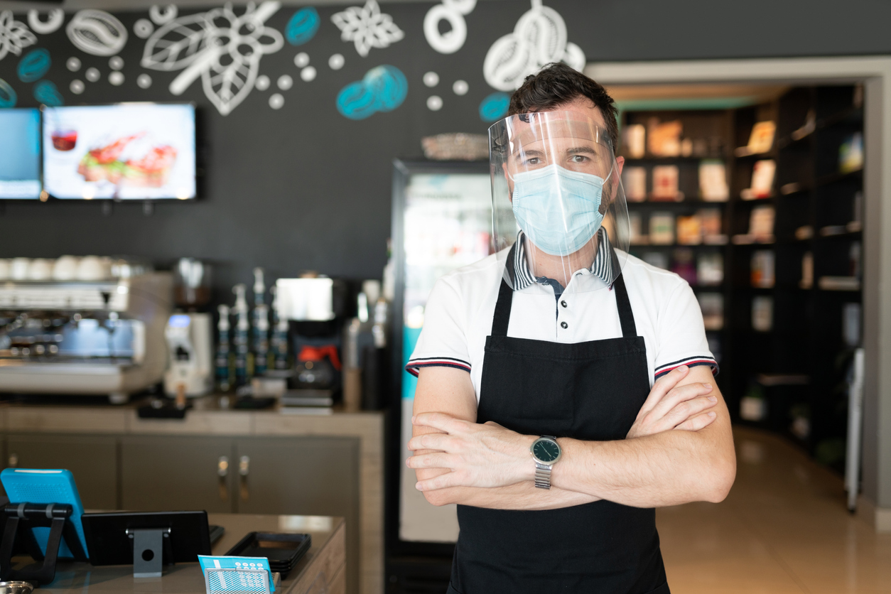 A waiter stands in a cafe with his arms crossed while wearing a face mask and a face shield.