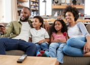 young black man, woman, and two kids sitting on couch watching TV