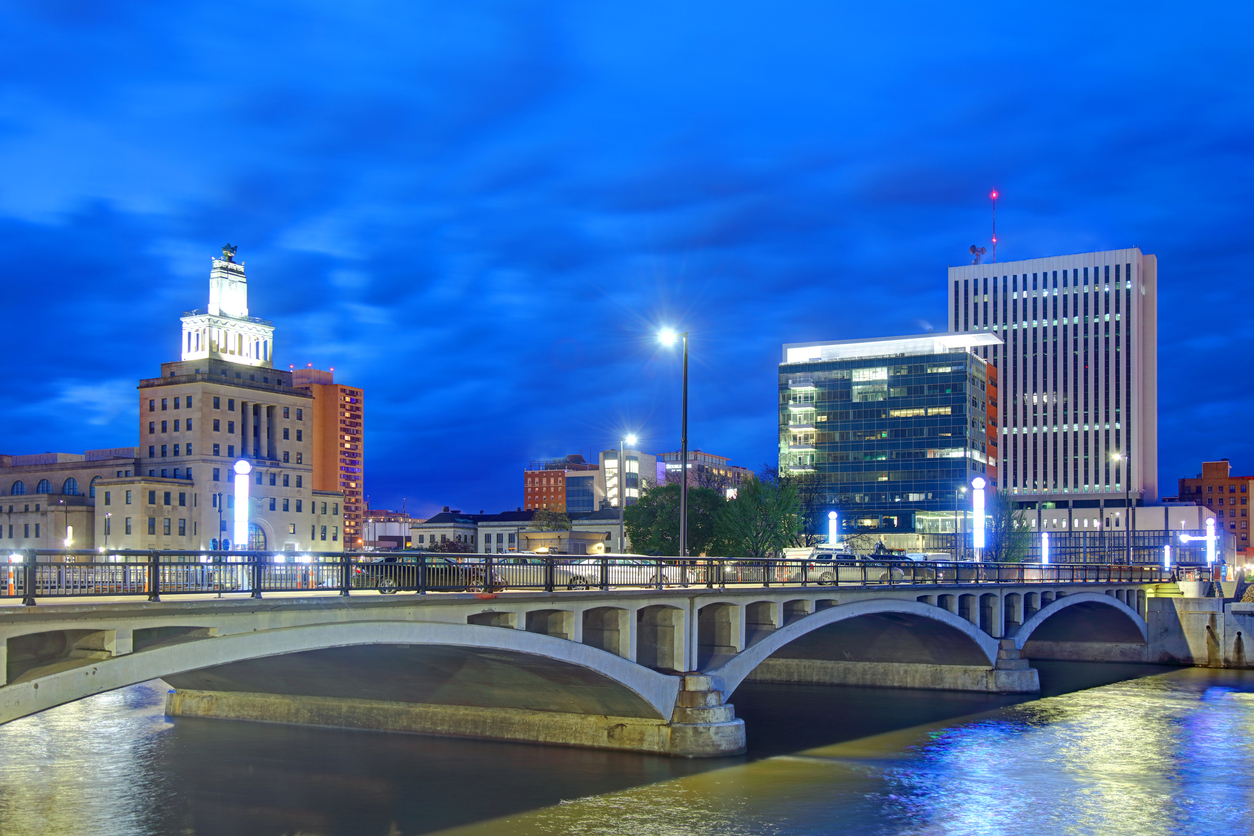 The skyline of Cedar Rapids, Iowa at night with a view of a bridge.