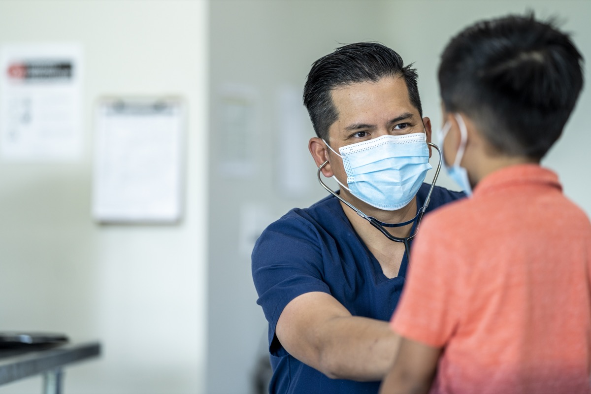 Male doctor wearing a mask and gloves during a checkup with a young, 8 year old boy because of the COVID-19 outbreak.
