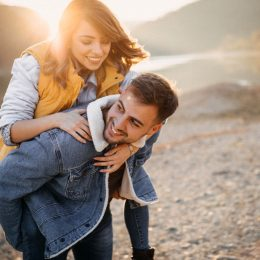 A young woman jumps on her boyfriends back on a lakeshore in autumn.