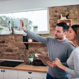 A young couple standing in their kitchen holding a clipboard and planning amazing home upgrades