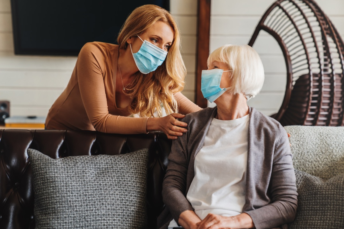 Senior woman in medical mask with social worker visiting her at home
