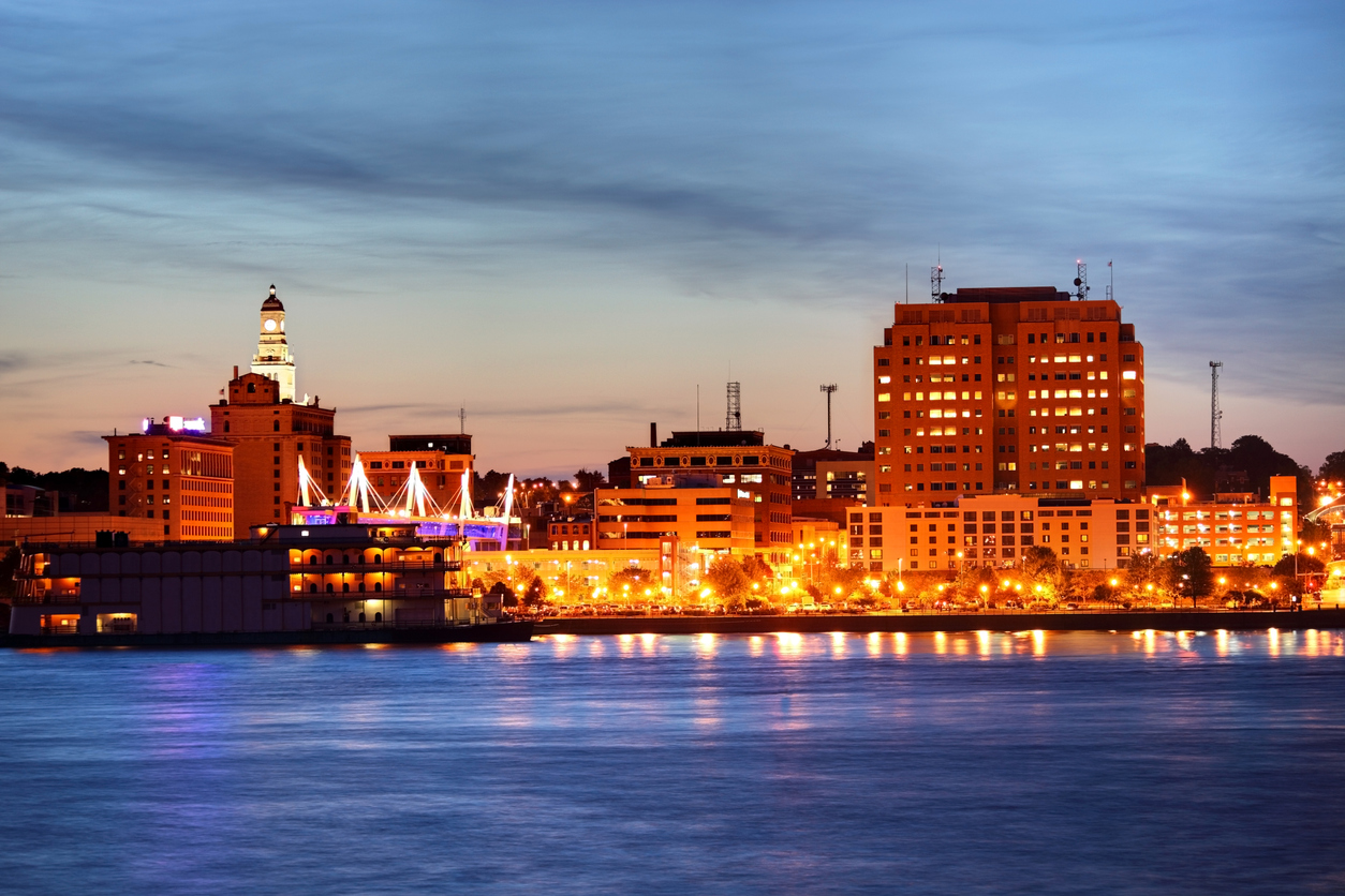 The skyline of Davenport, Iowa at sunset with the Mississippi River in the foreground