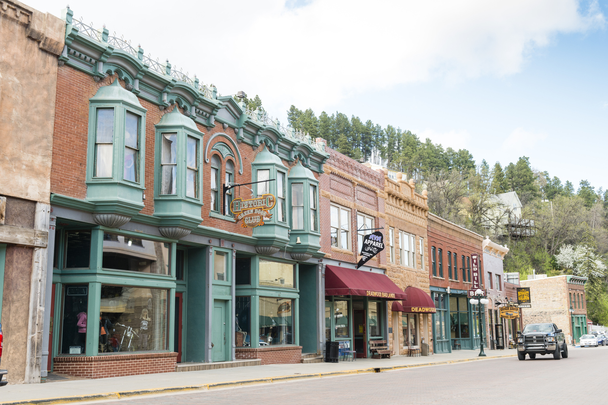The main street of Deadwood, South Dakota lined with shops and a passing vehicle.