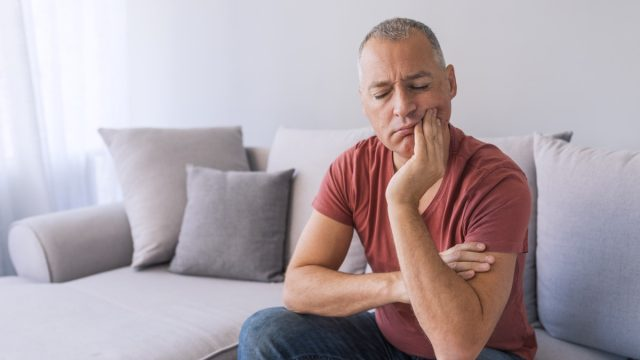 Photo of Depressed ill man having toothache and touching cheek. Mature man suffering from tooth pain, caries. Handsome gray hair male suffering from toothache, closeup. Portrait of casual 46s mature man toothache with painful expression, sitting on sofa at home,