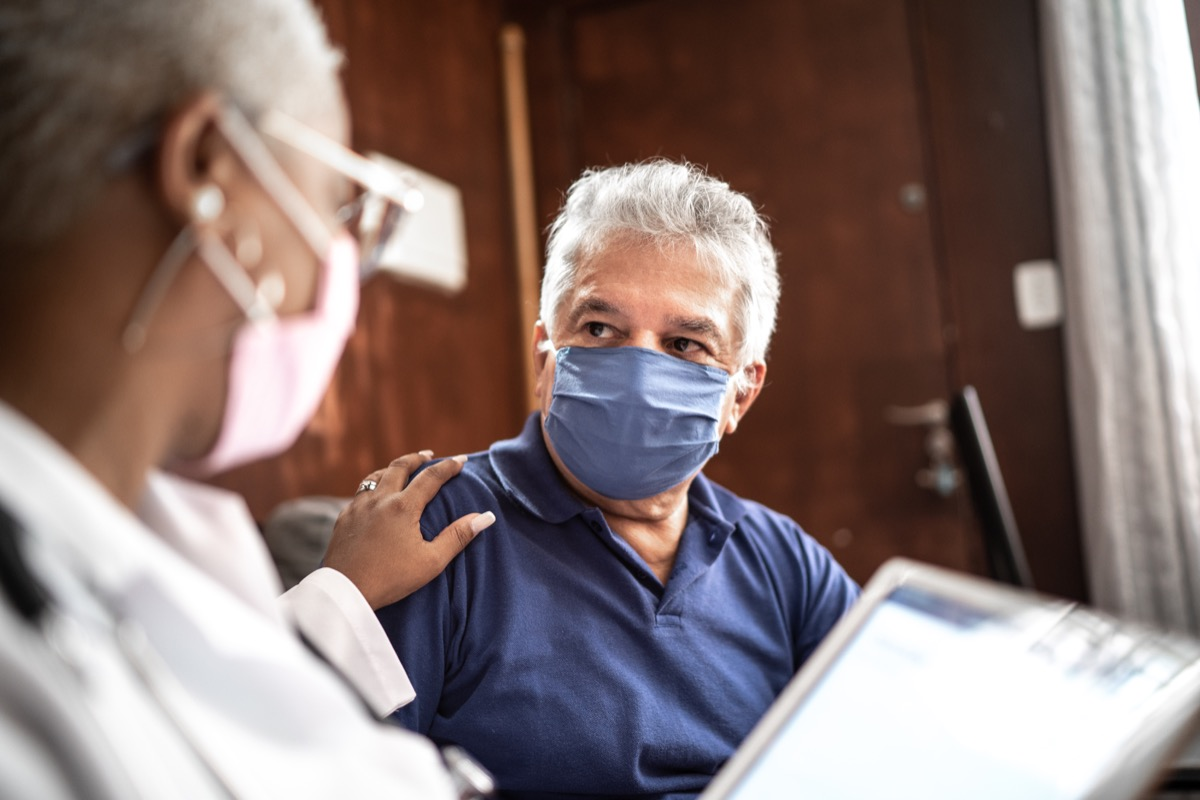 Doctor talking to senior male patient in a home visit